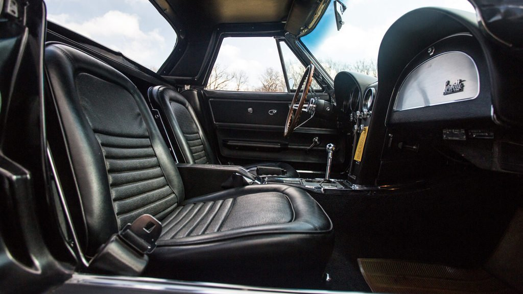 This 1967 Chevrolet Corvette is wearing Tuxedo Black paint and has the standard black vinyl interior, which are factory original, as are its dated black soft top and matching auxiliary hardtop, Rally wheels and non-DOT blackwall tires.