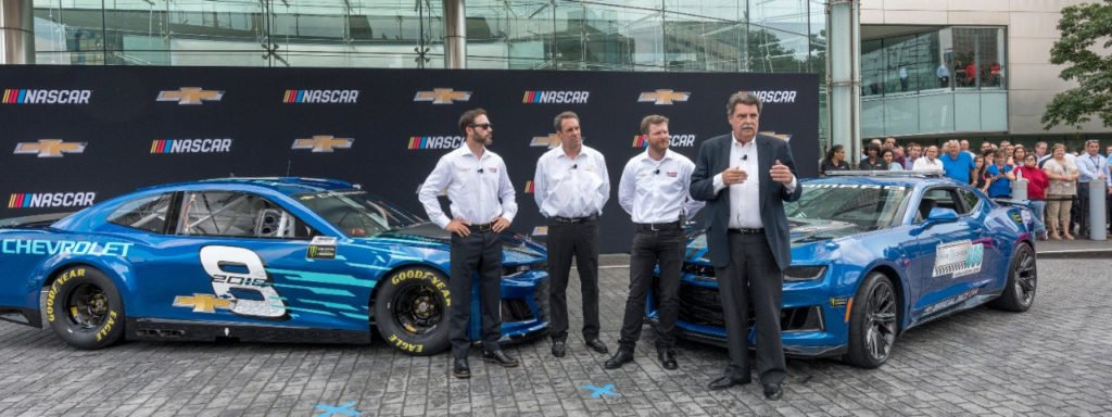 NASCAR Vice-Chairman Mike Helton (right) addresses the gathering as NASCAR Cup champion Jimmie Johnson (left) and Hendrick Motorsports teammate Dale Earnhardt Jr. (right center) and General Motors Executive Vice President Global Product Development Mark Reuss look on at the world debut of the Chevrolet 2018 Camaro ZL1 NASCAR Cup Race Car (left) Thursday, August 10, 2017 in front of the General Motors Renaissance Center Global Headquarters in Detroit, Michigan. The Pure Michigan 500 Camaro ZL1 Pace Car